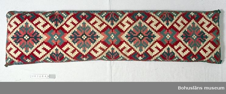 """Bänkdyna med översida vävd i röllakan (inplockat mönster), undersida av beige (oblekt?) linnetyg vävt i spetskypert. I hörnen dekorationer av små tyglappar; tryckt småmönstrat bomull, rutigt halylle, ylle. Översidans mönster är ett motiv som upprepas fyra gånger över längden Hårt stiliserade liljor sammanställda till ett likarmat kors (s.k. liljekors) inskrivet i en romb. Kring varje romb finns fyra S-former. Mellan romberna mindre motiv av romber med fyra """"ben"""". Halverade mönstermotiv sticker in som trianglar från långsidorna mellan de hela motiven i mitten. Liljan som huvudform finns enligt litteraturen i Bohuslän, södra Västergötland, västra Småland. Denna dyna är sannolikt från Bohuslän, troligen senare delen av 1800-talet. Färgerna i vävnaden är gultonat rött, gultonat ljusrött (skärt), blågrönt, mörkt och ljusare blått och vitt. De röda och skära garnerna är troligen färgade med krapp (har stark färg). Det blå möjligen färgat med syntetiskt färgämne, s.k. pariserblått. Om så är fallet är vävnaden tidigast från slutet av 1850-talet då syntetiska färgämnen kom.  UM020848 - UM020851 är funna i en stor plåtlåda vid flyttningen till det nya museet 1983 - 1984. Troligen ej tidigare märkta. Finns inte antecknade i inventarieförteckning från museet 1934. Ej blekt. Små bristningar här och var p.g.a. tidigare insektsangrepp.  Litteratur: Berg, Kerstin, Selma Johansson - väverska och hembygdsforskare i Södra Bohuslän, Skrifter utgivna av Bohusläns museum och Bohusläns hembygdsförbund Nr 41, Uddevalla 1991, sid. 191-193.  Västsvenska textilier å allmogeavdelningen Vägledning Jubileumsutställningen i Göteborg 1923. sid. 25-27.  Zickerman, Lilli, Sveriges folkliga textilkonst Utdrag ur föreningen för svensk Hemslöjd samlingsverk över svenska allmogetextilier Del 1 Rölakan, Stockholm 1937."""