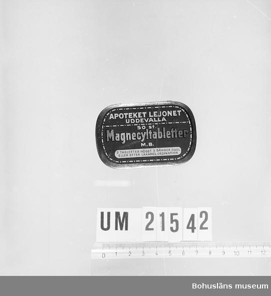 """594 Landskap BOHUSLÄN 394 Landskap SKÅNE  Asken innehåller ett antal om 100-150 glaskulor. Asken är märkt: """"Apoteket Lejonet Uddevalla 50 st. Magnecyltabletter MB."""" 2 tabletter högst 3 gånger dagligen, eller efter läkarens ordination. Gul metall med blåmålat lock med ovan angiven text."""