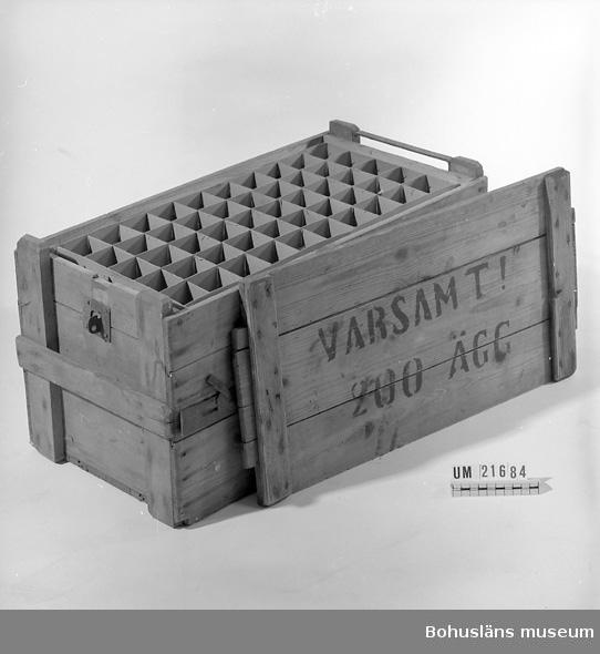 """594 Landskap BOHUSLÄN  Rektangulär låda med låsbart lock. Innehåller fack i papp i fem lager för totalt 200 ägg. En ribba i varje kortända som handtag. På ena kortsidan vid locket är det en metallanordning för stängning i vilket ett hänglås kan sättas. På locket är det tryckt med svart """"VARSAMT ! 200 ÄGG"""".  Omkatalogiserat 1997-01-23 GH.  UMFF 43:6."""