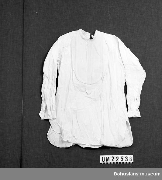 410 Mått/Vikt ! ÄL 54 CM 594 Landskap BOHUSLÄN  Vit frackskjorta, stärkbröst med snibb nertill, sprund i ryggen.  Trasig både i ryggen och framtill.  UMFF 125:7