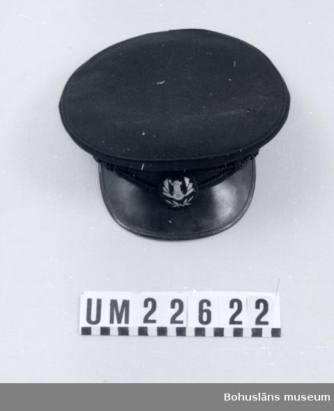 """594 Landskap BOHUSLÄN  Svart, dito skärm med grön undersida. Ripsband med mönsterranka broderat runtom, svart mössmärke med gul dekor, svart snodd av silke, fastsatt med två knappar som är prydda med en krona och tre stjärnor. Inne i mössan en grön etikett med texten: """"TIP-TOP mössan"""" i rött och """"Specialtillverkad"""" i vitt, samt en vit lapp med """"55"""" i blått. Insidan skyddad med celluloid som är fastsydd. Ovanpå mössan angrepp av mal.  UMFF 117:4"""