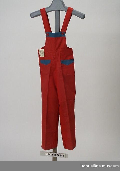 """594 Landskap BOHUSLÄN Röd byxa med bröstlapp i vilken hängslen knäpps. Två utanpåliggande fickor framtill. Knäppning i sidorna. På ficka och bröstlapp kantning av grönt bomullstyg. Mått benlängd 53 cm. Prisuppgiftslapp med tillverkningsuppgifter och """"storl. 6 år."""" Modell: """"Merit."""" Ur affärens varusortiment."""