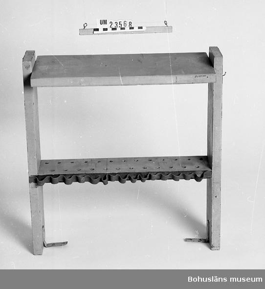 471 Tillverkningstid 1900-1950 594 Landskap BOHUSLÄN  Hylla i två avsatser. Grönmålad. Upptill vinkeljärn för att hänga den i tak eller dyl.  På övre hyllan hål och ett veckat läderband för borr, stämplar, verktyg mm.