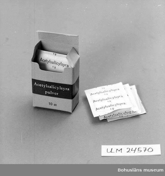 """Ask innehåller 10 st förpackningar med pulver. Text på pulverförpackningarna:""""Acetylsalicylsyra 1 g"""". Asken är gulgrå  med ett band med blågrått runt om.  Text sid 1:""""Acetylsalicylsyra pulver 10 st"""".  Text sid 2:""""Varje pulver innehåller 1 g acetylsalicylsyra"""". På en kortsidan står det tryckt """"DO 45"""". På locket/fliken finns en gul klisterlapp  med svart text:""""APOTEKET FJÄLLBACKA"""". Förvärvsort, se Placering.  Materialet insamlat i samband med byggandet av basutställningen Bohusläns museum 1984. Framlidne stenhuggaren Henrik Trygg 1894-1980, ogift man hade bott i denna lilla stuga i Bottna, norra Bohuslän.  Panel från huset användes i utställningen. Några få möbler stod kvar i stugan, bl.a en enkel chiffonjé. Chiffonjén stod i många år som rekvisitamöbel vid folkmusikavd. i basutställningen.  I arkivet Bohusläns museum finns en intervju utförd 1983-02-17 med Arne Trygg. Foton i Bildarkivet, Bohusläns museum. Negativ nr UMFF 3:213"""