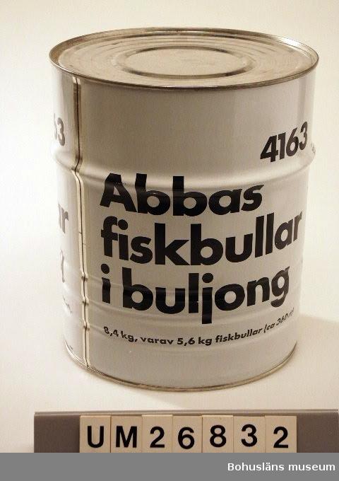 """Cylinderformad burk i vitt med tryckt text i svart direkt på plåten. Text: """"Abbas fiskbullar i buljong. 8,4 kg varav 5,6 kg fisk bullar (c;a 360 st)"""" och """"4163"""" samt innehållsdeklaration."""