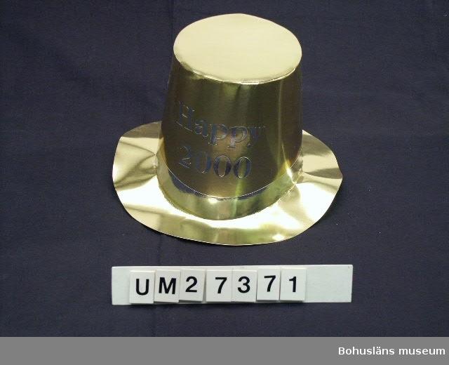 """* Diameter avser kullen.  Hög guldfärgad cylinderhatt av papp med silverfärgat hattband och texten:"""" Happy 2000"""". Oanvänd i skyddsförpackning. Inköpt på Timari  i Uddevalla för 16.50.    För information om Millennieinsamlingen, se UM27360."""