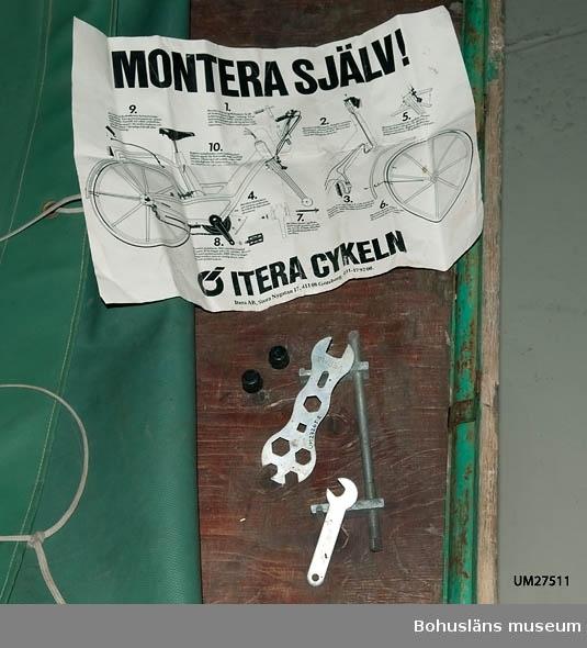 Måttuppgifter flaket: 195 x 195 cm; höjdmåttet avser höjd vid styret. Grön presenning, fästad i flakets bakre del. Mopeden är inköpt i Strömstad 1973 och använd på Sydkoster till slutet av 200 Mopeden ingår i insamlingen i projektet Moderna skärgårdsbor, UM027511 - UM027595 och kommer från Sydkoster.