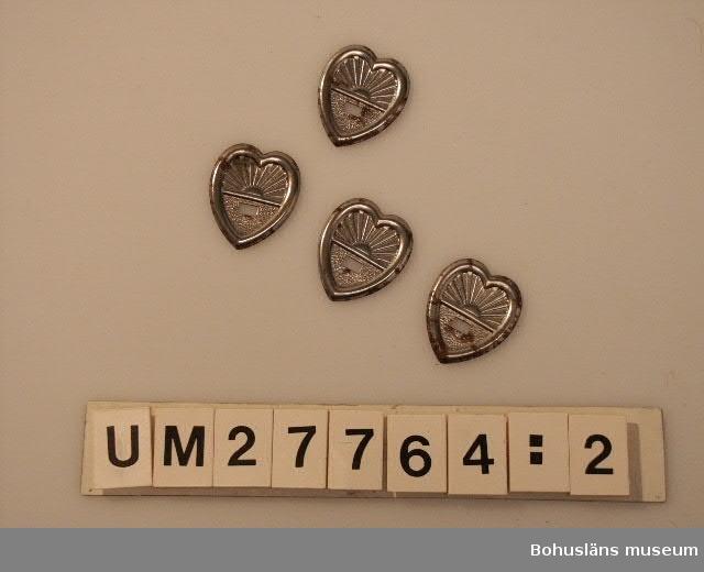 394 Landskap Bohuslän 594 Landskap Bohuslän 503 Kön MAN  UM27764:1 - Fyra profilerade kistfötter, ett par mindre, ett par större av trä målade med silverfärg. Av samma typ som använts på kistorna UM27759 - UM27763.  UM27764:2 - Fyra gjutna bärhandtag med skyddspapper om. Förnicklad handtagsdel, silvermålade fästen. Av samma typ som använts på kistan  UM27759.  UM27764:3 - Fyra gjutna bärhandtag med dekormönster. Förnicklade. Korrossion. Av samma typ som använts på kistan UM27760.  UM27764:4 - Fyra runda och utsirade manschetter av formpressad tunn metallplåt, belagd med ett silvrigt ytskikt för kistlockets skruvhål. Av samma typ som använts på kistorna UM27759 och UM27760.  UM27764:5 Fyra hjärtformade utsirade manschetter av formpressad tunn metallplåt, belagd med ett silvrigt ytskikt för kistlockets skruvhål.   Kisttillbehören kommer från Edward Carlssons kistillverkning i Grundsund. Materialet är beställt av honom att användas till de kistor han tillverkade. Det har inte framkommit några uppgifter om varifrån han beställde materialet.   För ytterligare uppgifter om kistorna, försäljningen och om tillverkaren, se UM27759.
