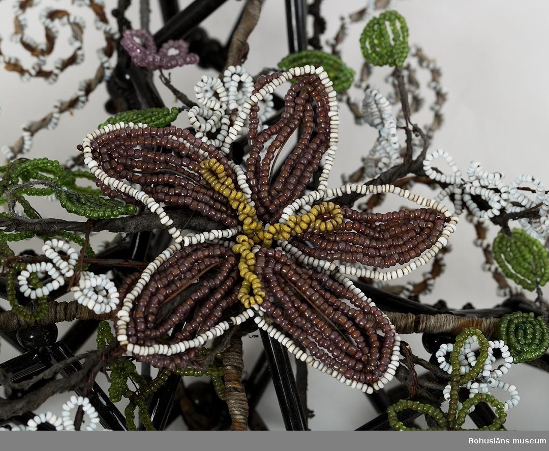 """Pärlkors gjord på stomme av järntråd i en konstfull hopflätning i tredimensionell form, högst där korsarmarna möts. Järntrådsstommen har ursprungligen varit helt omvirad med papp, dels svartfärgad, dels i andra, ursprungligen kulörta färger. Pappen har fallit bort på många ställen. Stommen är därefter klädd med svarta glaspärlor - stavar och runda samt med vita och svarta små pärlor, uppträdda på textil tråd som virats runt stommen. Korsmitten pryds av ett arrangemang med blomster och blad av småpärlor  i violett, brunt, gult och grönt. Utmed korsarmarna sitter strödda blommor och blad i violett, vitt och grönt. Järntråden bitvis rostig.  Ur följebrev, skrivet av Rune Hammarskog, yngre bror till den avlidne: """"Pärlkransen och pärlkorset har förvarats på en vind i ett hus i Håvedalen, Norra Bohuslän. Kransarna och korset var tillägnade gossen Holger Hansson, son till Ester och Hans Nilsson, Håvedalen. Holger var född den 22 april 1917 och avled den 16 september 1928, alltså 11 år gammal. Begravningen ägde rum i Skee kyrka någon vecka efter dödsfallet. Kransen överlämnades då av Holgers morföräldrar, f.d. gränsridaren Olof Martin Carlén och hans hustru Emma. Givaren av korset är okänd. Vid samma tillfälle lämnades även en pärlkrans av en granne till familjen, snickaren Anton Mattsson och hans hustru Maria. Anton Mattsson hade troligen även tillverkat Holgers kista. På Skee kyrkogård fanns i slutet av 1920-talet och början av 1930-talet ett flertal gravar som var prydda med pärlkransar/kors. En del kransar förvarades i en trälåda som var täckt av en glasskiva. Kransarna var ömtåliga och skadades ofta. De togs därför bort och försvann så småningom helt från kyrkogården.""""  Holger Hansson var sjuklig från födseln och avled troligen i hjärntumör. Dessa gravprydnader bör ha plockats bort från graven redan under hösten, kanske för att läggas tillbaka under sommarhalvåret. Därefter har de förvarats på vinden i huset som ligger en halv mil från norska gränsen. Gåvan består även"""