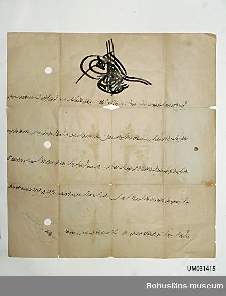 Tunt trähaltigt papper, något snett skuret och i 12 vikningar.  Uppgifter på framsidan/insidan: Text på arabiska skrivet med svart bläck med guldglitter fästad på färgen, täckande 4/5 av arket i jämn och välskriven kalligrafi där varje rad avslutas snett upp åt vänster. Överst en stor centralt placerad anfang (namnschiffer). Fem rader text undertecknad med en namnteckning.  Uppgifter på baksidan på vad som har varit utsida av fermanen då den varit ihopvikt till storlek motsvarande ungefär ett A5-kuvert: Skrivet med svart bläck: kortfattad arabisk utanpåskrift på fyra vikningar.  Skrivet med blyerts Bylgia  Vikningar, missfärgning efter vikningar, fläckar, gulnat, sprucket i vikningar. Tre runda och ett mångformigt hål, troligen efter stämplar eller figurer med extra mycket färg som fallit bort.  Ur Nationalencyklopedien Internet 2009: firma´n, ferman (av persiska ferman, vilket motsvarar sanskrit pramana 'befallning'), framför allt i Osmanska riket benämning på viljeyttring av sultanen, såsom order, privilegiebrev, förordnanden o.d. Firman skrevs alltid ut i omsorgsfull kalligrafi och försågs upptill med sultanens dekorativt utformade namnchiffer, tughra.   Ur Svenska Akademiens Ordbok: FIRMAN --- [jfr t. ferman, firmane, eng. firman, av pers. ferman, motsv. sanskr. pramana, befallning] i muhammedanska länder (i sht Turkiet): viss från suveränen (l. hans Ställföreträdare) utgången befallning l. order l. kungörelse l. fullmakt, öppet brev (Ofta tjänande som pass).       I