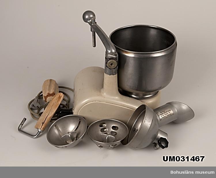 Hushållsassistent från 1940-talet av märket Electrolux. Stomme med elmotor av ursprungligen beigemålat gjutjärn med löstagbar arm, armfäste och övre stativ av aluminium. Dämpande gummiknoppar undertill och på ena sidan. Rostfri, löstagbar skål. Elsladd av grått gummi med kontakter av bakelit. Tillhörande redskap i metall och björk; blandare, degrulle av trä, rivjärnssats och skrapa av trä. Givaren kommer att komplettera med grönsakskvarn, köttkvarn, korvhorn.   Efter många års flitig användning var färgen på maskinen väldigt sliten varför den målades om. På sidan har texten ELECTROLUX funnits.