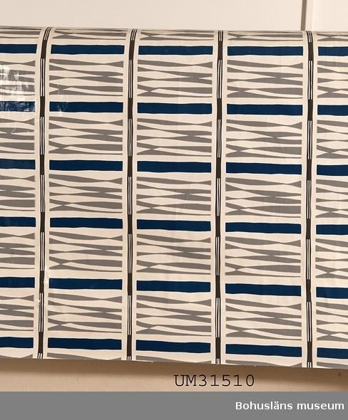 Rektangulär plastduk av PVC-skikt på bomullsväv från 1950-talet. Vit botten med tryckt abstrakt mönster i mellanblått och två grå nyanser. På baksidan en liggande oval stämpel tryckt i vitt, inuti med texten: VÄVPLASTDUK FRÅN Anneberg DUKSPECIALISTEN Se Bilagepärmen UM31510 för reklamblad från företaget.  Duken har använts till matbordet i allrummet i en sommarstuga i Sundsandvik, Bohuslän. Duken var avpassad för bordet i utdraget skick. I allrummet finns panoramafönster mot fjorden, på motsatt vägg ett högt placerat långsmalt fönster,  en murad öppen spis, lackat trägolv med smala plank, vita väggar och tak. För interiörfoto, se UMFA55058.  Föremålet har använts av familjen Abrahamson i deras sommarstuga i Sundsandvik, byggd 1939. För ytterligare upplysningar om förvärvet, se UM031385.