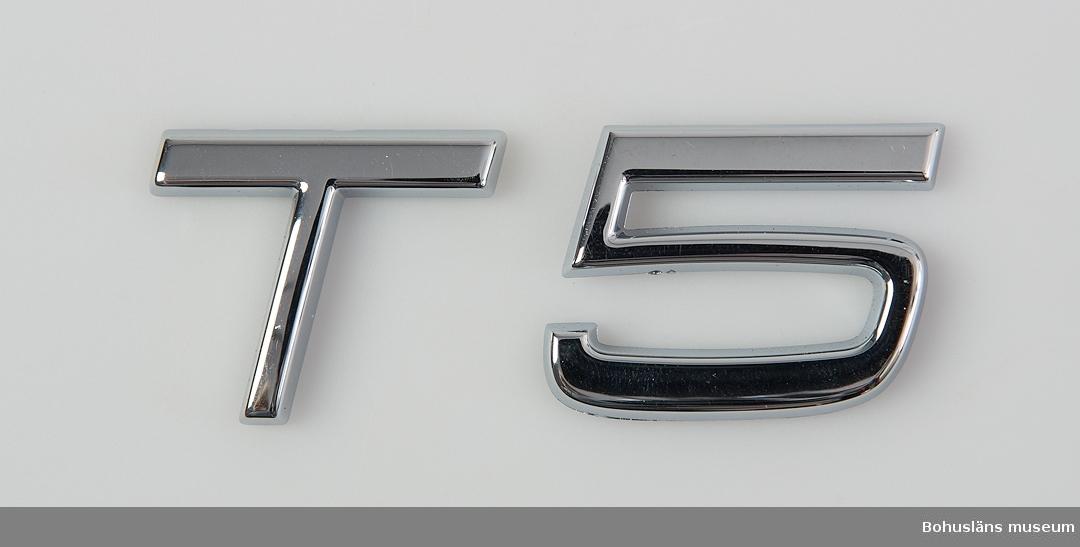 Föremål från bilfabriken Pininfarina / Volvo i Uddevalla, Monteringsfabriken. Motoremblem, fästs under höger baklykta.  T5 är till bensindriven motor.