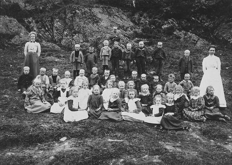 """Enl. tidigare noteringar: """"Andra klass 1904 vid Ölseröds skola.  Lärarinna Stina Jonsson längst till höger. Sigrid Johansson (-Olsson) sitter 5:a från höger. Repro 1985 av foto tillhörande Sigrid Olsson f. Johansson Dalby, Henån."""