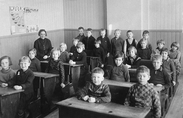 """Enl. tidigare noteringar: """"Interiör från klassrum 2:a klass småskolan Slättens skola Lysekil 1939. Lärarinnan frk Nilsson.  I tredje raden längst till höger Gunvor Karlsson (senare gift: Grundberg) syster till Vivi Russberg.  Repro 1985 av foto tillhörande Vivi Russberg, Uddevalla""""."""