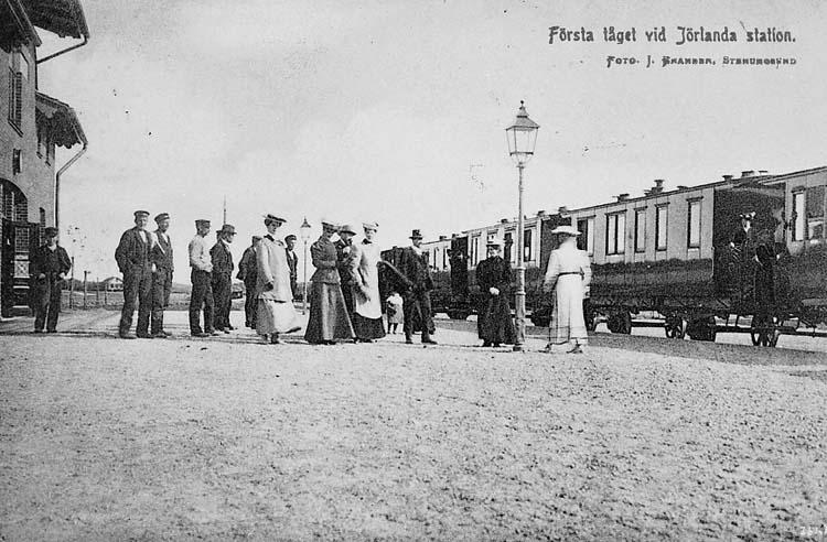 """Text på kortet: """"Första tåget vid Jörlanda station. Foto J. Bramber. Stenungsund""""."""