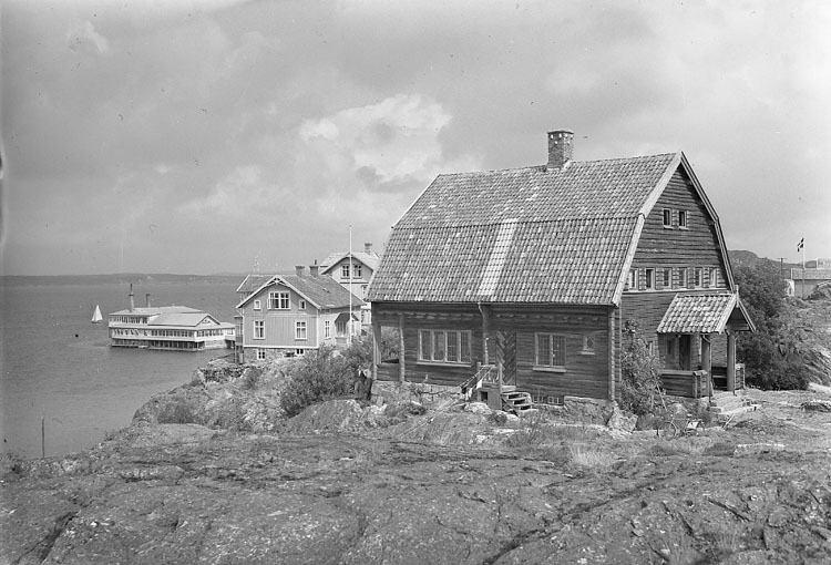 """""""Fiskebäckskil stugan på berget Bohuslän"""" enligt AB Flygtrafik Bengtsfors.  Det timrade huset i förgrunden är sommarhuset med ateljé som konstnärerna Carl och Berta Wilhelmson lät uppföra år 1910. Arkitekt Ivar Callmander, Stockholm."""