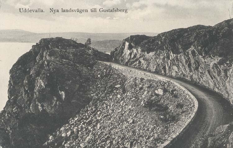 """Tryckt text på kortet: """"Uddevalla. Nya landsvägen till Gustafsberg."""" """"Uddevalla Pappershandel, Hildur Andersson."""""""