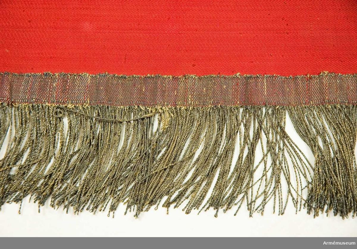 """Grupp B I. Duk av merceriserad bomull? vävd i kypert med röd botten. Inplockat vitt fält i mitten med stjärnan och månskäran. Silverband i kanten invävt. Franstrådar är fastträdda i duken, 5 cm långa. För fastsättning vid stång finns en """"strumpa"""" med hätta. Stång saknas."""
