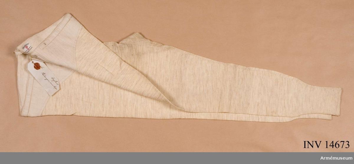 """Grupp C I Av beige ylletrikå. På framsidan sprund med tre  knappar. På båda benändarna skaft av stickat ylle. På kalsongernas baksida vid bältena, en firmaetikett av bomullstyg med påskriften """"The Harvester reg (British make) guaranteed  underwear Extra durable two threads"""".  Kalsongerna har pappersetikett med påskriften """"England, kalsonger, manskap""""."""