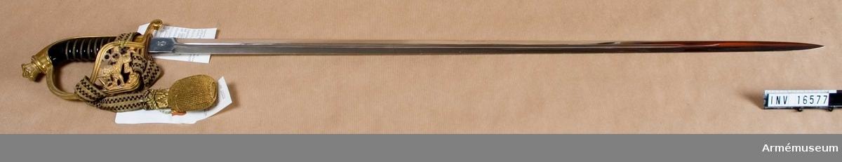 Rak tvåeggad klinga med blodrand och förnicklad. Märkt med Solingers stämpel: visirhjälm. Bredd vid fäste: 22 mm.   Fäste av förgylld mässing med dekor av Finlands vapen: lejon.   Kavel av svart bakelit, konstmassa, lindning av förgylld mässingstråd. Tillv.nr: 93.  Vapnet tillhör uniform AM 9474-6 och koppel AM 16463.