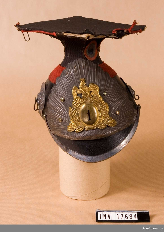 """Grupp C. Mössa av svartlackerat läder och skärm med järnbeslag. På  mössans övre del finns ett mörkrött band, 3,5 cm brett. Foder av svarta läderbitar hopbundna med snören. Hakremmar av läder med järnspännen. De är fästade vid mössans botten. Hakremmar  med fjäll saknas; på båda sidor finns två rosetter i form av lejonhuvuden med krokar för att hänga upp hakremmarna. På mössans framsida finns en vapenplåt av järn och en annan av mässing ovanför. Den sistnämnda har formen av en tupp med regementsnumret (""""1"""") i mitten. Mössans överdel består av ett fyrkantigt lock (längd och bredd 18 cm) med röda snören längs kanterna. På vänstra sidan finns en rund kokard i tre färger, röd, vit och svart. Revär av svart kläde, kringsytt med röda snören, varav det finns en liten bit kvar. Tuppen är ett speciellt franskt, republikanskt,  utmärkelsetecken.  Litteratur: Handbuch der Uniformenkunde, Knötel / Sieg. Hamburg 1937 sid 181. Lanzenreiter: År 1870 hade man planerat en genomgripande förändring av den franska ulanuniformen, men denna förändring  blev endast till ringa del genomförd. Ulanmössan (tschapka) blev svart. Enligt kapten W. Granberg."""