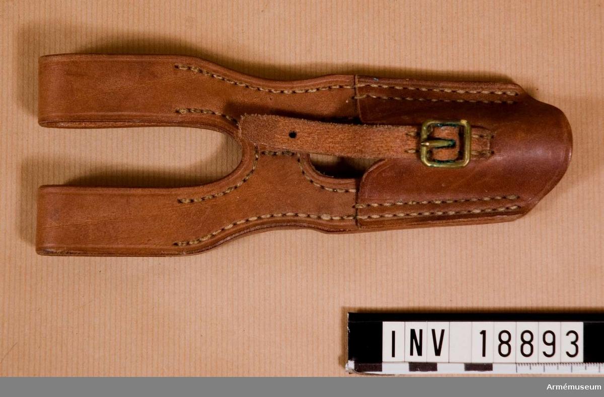 Grupp C II. Av brunt läder med två öglor för livrem och hylsa för bajonetten med rem och spännen för att koppla bajonetten till hylsan. På hylsans baksida finns stämplar på japanska språket.