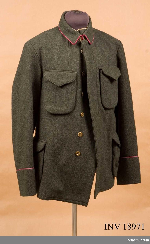 """Grupp C I. Ur uniform för manskap, Norge. Bestående av vapenrock, långbyxor lägermössa, vantar, strumpskaft, skidkängor, livrem, med patronväskor och bajonetthylsa. Vapenrock (blusen) av gröngrått kläde (mörk kaki). Enradig med 6 bruna benknappar som knäppes innanför =dold knäppning. Fickor, 2 st, påsydda på rocken, sidofickor och två bröstfickor också påsydda. Alla fickorna har treuddiga lock, som knäppes med knappar. Vid nedre kanten på framsidan finns en ficka för paket innehållande första hjälpen, sanitetspaket. Foder av vitt bomullstyg med en innerficka och en liten ficka av kläde. På ryggen en stämpel med text """"III, R I""""  =III bataljon, """"Smaalenenes infanteriregemente n:r 1 (Fredrikstad) =första division. Knappar- bruna av ben, 6 st på framsidan och 4 st på fickorna, d:20 mm. Krage, dubbelvikt av samma kläde och knäppes med 2 hyskor och hakar. Fodrad med grönt tyg och kantad med karmosinröd passpoal vid kragens nedre kant. Ärmuppslag rakskurna, h:120 mm. Kantade med karmosinröd pass- poal. LITT  Handbuch der Uniformkunde, professor R. Knötel, Hamburg 1937. Sida 260. Redan år 1903 försökte man i Norge införa kakifärgad uniform, men inte förrän 1912 lyckades man slut- giltigt införa den gröngråa uniform, som nu är enhetlig för såväl värnpliktigt manskap som officers- och underofficers- kåren för dagligt bruk. Uniformen består av vapenrock (blusen) med påsydda två sido- och två bröstfickor, med dubbelvikt  liggande krage. Både krage och ärmuppslag äro kantade med karmosinröd passpoal. Den Norske Haer. Verlag von Moritz Ruhl in Leipzig. År 1932. Sid 11 Uniformsbeskrivelse. a) den fjell- grå uniform (feltuniform). Fältvapenrock (""""jacke"""") är änkel- knäppt, ärmuppslagen rakskurna med karmosinröda passpoal,kragen liggande och kantad med samma karmosinröda passpoal. Bilaga. Bilder i färger 2:a sidan: Infanterist med fältutrustning.Enl kapten W Granberg 1953."""
