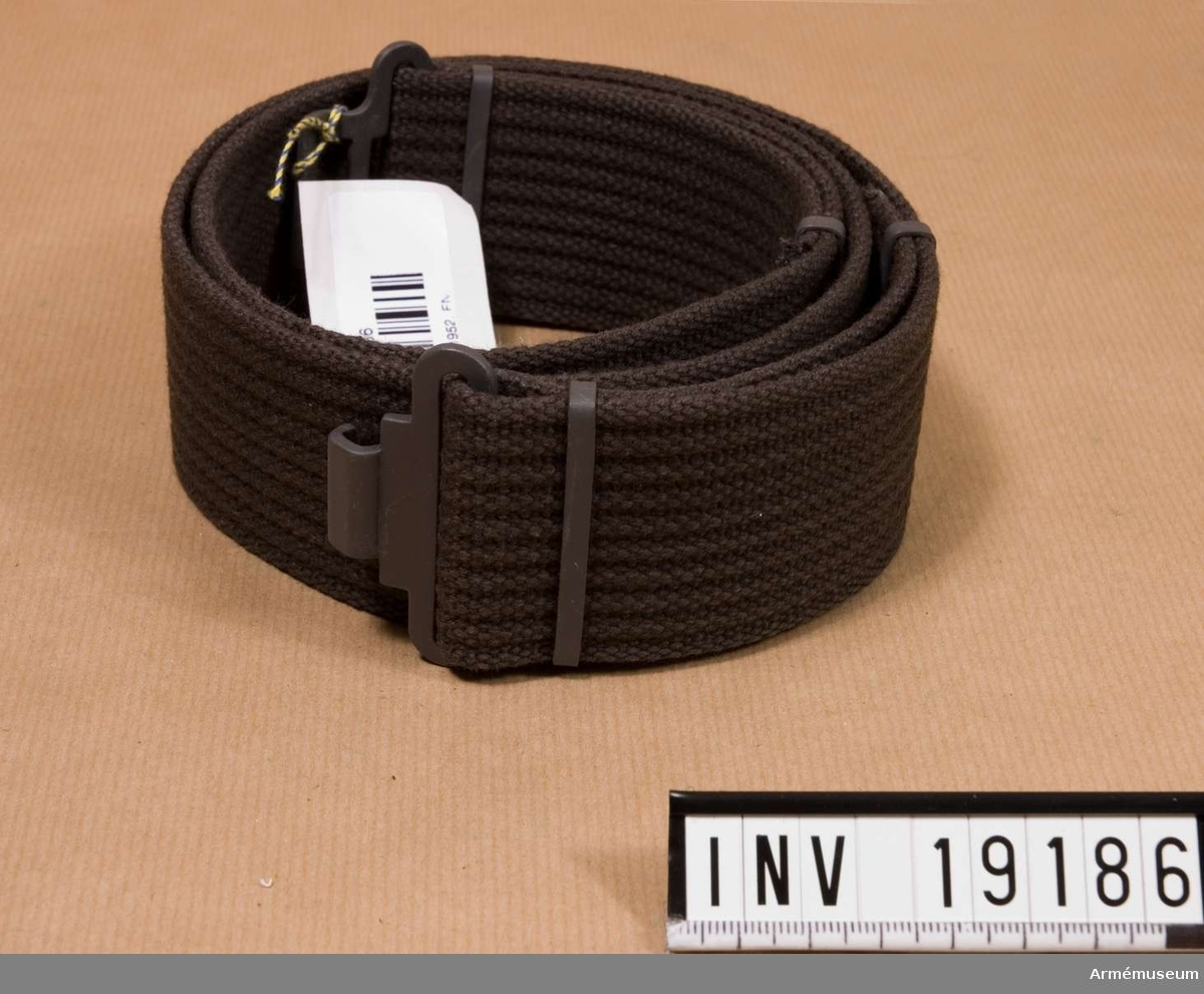 Samhörande nr är: 19180-9, hjälm, mössor, halsdukar m m. Av grått vävt band med grått metallspänne och söljor.