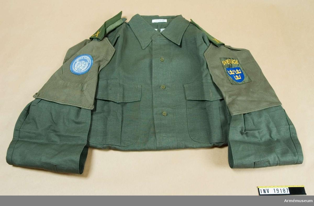 Djungelgrön fältskjorta med  bröstfickor och axeklaffar. Axelklaffhylsa på båda axlarna. Armhylsa med FN-emblem på höger ärm och armhylsa med nationsmärke på vänster ärm.Skjortan bärs uppknäppt i halsen med eller utan halsduk.