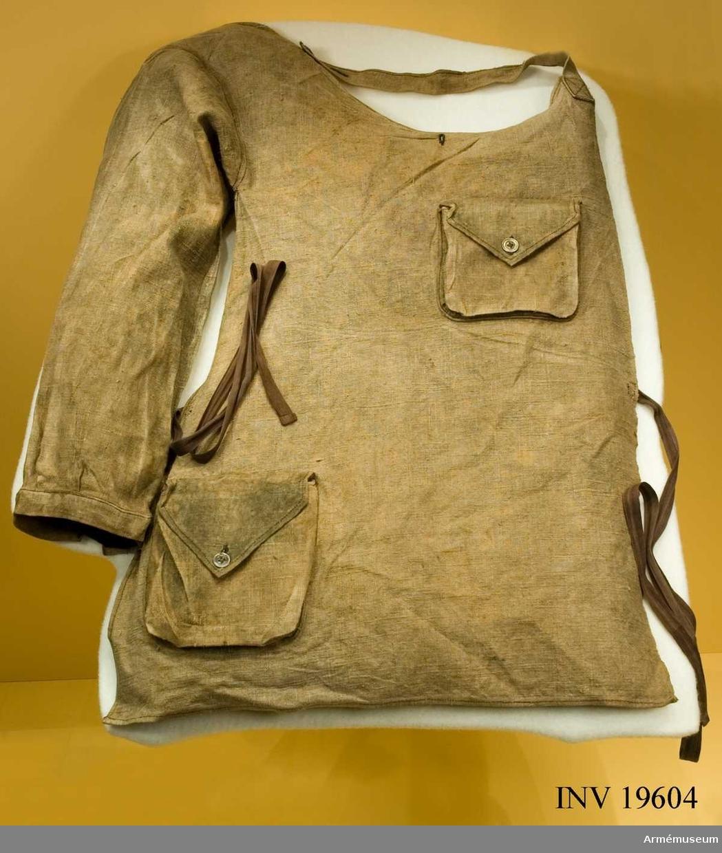 Förklädet är tillverkat i linne. Färgen är grönaktig. Framsidan är sydd i ett enda stycke och med en ärm till höger för att täcka framsidan av kroppen och höger arm. Ärmen är försedd med linning och två knappar och knapphål. Ett band finnns att fästa runt nacken.   Förklädet har två bälgfickor med en extra fodring på den övre. Den övre fickan är förmodligen avsedd till att förvara något varm inuti.