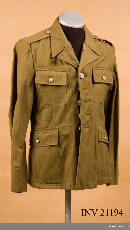 """Grupp C I. Ur uniform för menig vid infanteriet för sommarbruk. Av bomullstyg i kakifärg med 7 knappar på framsidan. Axelklaffar av kakityg, b:50 mm, l:120 mm, fastsydda vid ärm-sömmar och fästade vid rocken med knappar. Fickor, alla påsydda: två bröstfickor och två sidofickor med fyrkantiga lock och försedda med knappar. Foder saknas. På tygets insida finns stämplar; på H sida oläslig så när som på """"år 1947"""" och på V sida även oläslig, endast """"år 1946"""" synligt. Vid nedre kanten """"Man. dep. int"""" - vidare icke läsligt - och sedan """"år 1946"""" , """"3"""" - storlek. Knappar av vitmetall med heraldiska polska statsvapnet, men på örnen finns inte krona. Knapparna är 2 cm i diam.: 7 st  på framsidan, 2 st på ärmuppslaget, 1,5 cm i diam. 4 st på fickorna och 2 st på axelklaffarna. Kragen liggande, med hyska och hake. Foder av samma kakityg."""