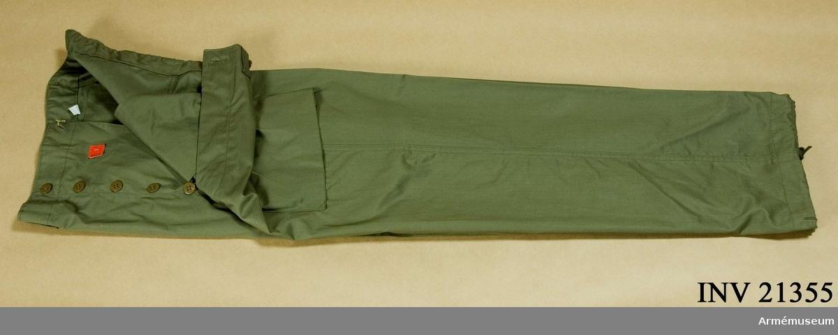 """Grupp C I. Av impregnerat silkestyg i kakifärg med 4 fickor; två sneda fickor på framsidan, två stora fyrkantiga på baksidan, täckta med ficklock, som stängas inuti med en tygbit och knapp. Alla knappar av ben, kakifärgade, d:15 mm, 5 st på sprundet, 6 st för hängslen och två för bakfickorna. Byxorna har fastsydda löpare. På sprundet och i båda framfickorna finns en röd pappersetikett med påskriften: """"2613, 32M32, 1-4364""""."""