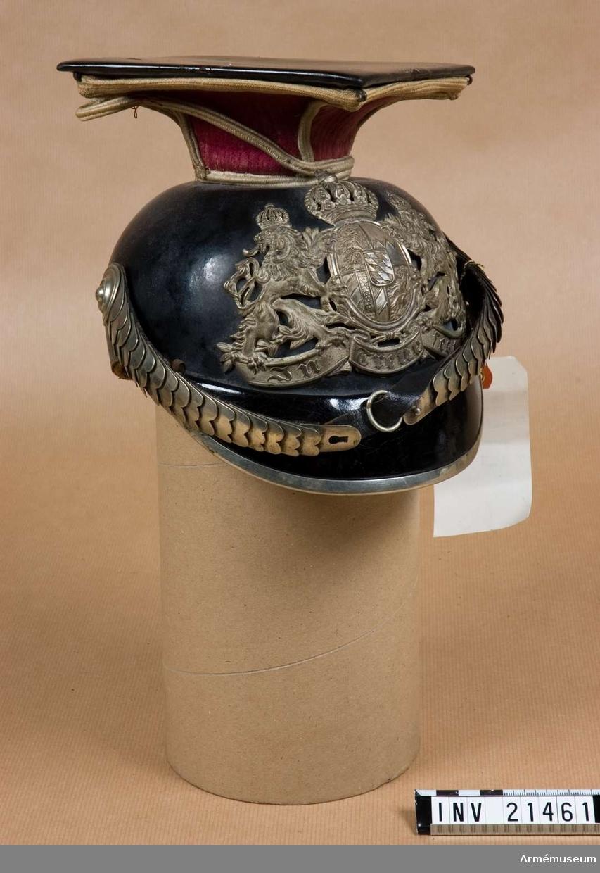 Grupp C I. Mod. 1886. Av svartlackerat läder med avrundad framskärm med beslag av nysilver. Alla metalldelar är av nysilver. Foder av skinnbitar. Hakremmar av läder med ciselerade fjäll, två rosetter samt spänne.