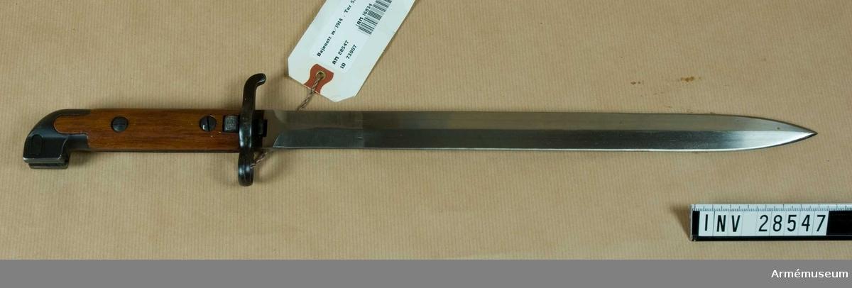 Grupp E II. Bajonetten har tveeggad klinga. Knappen och parerstången är brungjorda. Den förstnämnda har upptill en framåtvänd förlängning, i vilken bajonettspärren är anbringad.  Kalven beklädes på vardera sidan av en valnötsskena, vilka skenor förenas med tången och med varandra genom ett par skruvar, vilka inskruvas i på den inre sidan befintliga, med skåror försedda muttrar.  Skruvhuvuden och muttrar är nedfällda i jämnhöjd med träets yta. Parerstången är framtill utvidgad och är där försedd med hål för bajonettskenans förlängning.  Baktill är den mot änden litet nedböjd. På yttersidan finns en spärr, som fasthåller bajonetten i baljan. Spärrens utlösningsknapp ligger delvis infälld i valnötsskenan litet ovanför och spärrtanden ligger litet nedanför parerstångens mitt. På stångens mitt är inslaget 3/K 4 No 127.  Tillverkningsnummer 530.  Samhörande nr är: 28546-48