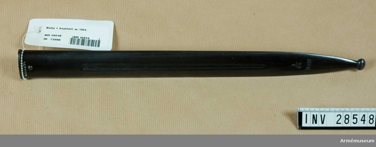 Grupp E II Baljan är av brungjord stålplåt och har längs mitten på vardera sidan en försänkt ränna. På utsidan har den knapp för bärhylsan.J. Alm.  Samhörande nr AM.28546-8