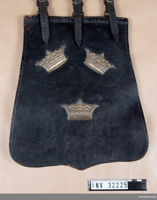 """Grupp C I. Ur uniform för manskap vid Livgardet till häst, 1814-20. Består av dolma, päls, spännhalsduk, byxor, knutskärp, tschakå med plym  och kordong, pompong, vapenplåt, tjällband, knappar, sölja, kartusch med kartuschrem, sabelkoppel, sabeltaska med 3 remmar, sabel med balja, sabelhandrem, stövlar med sporrar, handskar. PUBL  AMV Meddelande XIX, s.112.  Tillhörande modelletikett med text: """"Af Kongl. Majt Nådigst fastsäldt Modell å Sabeltaska med remmar för Lif Gardet till Häst, enl. General Ordres af d. 16. Julii 1814."""". På andra sidan: """"Sedan Kongl. Majt den 19. Augusti 1845 för detta Regemente i Nåder fastställt förändrade Modeller till Remtyg, äfvensom att Sabeltaskor icke vidre Skola af Regementet begagnas, har denna Modell upphört att vara gällande.""""."""