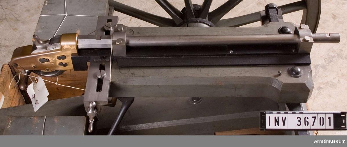 Grupp E IV a.  Konstruerad av civilingenjör Saxenberg 1868. Patronerna, vilka är enhetspatroner, måste för hand tas ur magasinen - tvenne, en på vardera sida befintlig, med patronlägen försedda lådor - som insätts i pipan, som är försedd med en vanlig Remingtonbakladdningsmekanism.  Samhörande nr är 36701-2, kulspruta, lavett.
