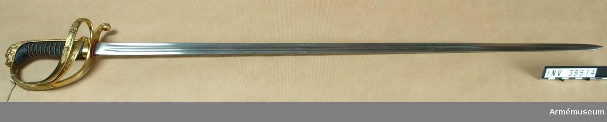 Grupp D II Försöksmodell, enligt chefens för Svea Artilleriregementes förslag.Klingans bredd upptill 23 mm. Klingan tillverkad i Mölntorp. Fästet tillverkat i Stockholm.Klingan är rak samt till större delen av sin längd eneggad och försedd med två ganska breda och djupa blodrände men får omkring 22 cm från udden egg även på ryggsidan samt svagt utpräglade ryggar. Upptill på kvartsidan står G.E SVALLING & Cni, MÖLNTORP. Fästet har beslag av förgylld mässing. Kaveln är klädd med svärtat fiskskinn och har 12 refflor, i vilka två av två parter hopsnodda förgyllda mässingstrådar är anbringade. Båda trådarna är snodda åt samma håll. Baktill har kaveln ryggbeslag, som upptill övergår i en i form av ett lejonhuvud ciselerad kappa. Lejonets man fortsätter ned på ryggbeslaget, vilket längs kanterna prydes med en ingraverad rand, och från kanten går halvcirkelformigt krökta ränder upptill denna rand. Mitt i varje sådan halvcirkeln sitta tre prickar. Nedtill omgives kaveln och ryggbeslaget av ett ringliknande, 1 cm brett, med två ingraverade linjer prytt beslag.Parerstången är baktill nedböjd och slutar i en ciselerad knapp, men övergår framtill i båge i handbygeln. På  handbygelns mitt finnes en sköld med tre kronor, vilken sköld omgives av en trofé. Upptill vid kappan prydes handbygeln av några enkla, ciselerade ornament. På terssidan utgå från parerstången ett par spänger, som gå till handbygelns mitt. Ungefär på mitten är dessa spänger ornerade med en hand, som håller en blixt, i ciselerat, upphöjt arbete på punsad botten. På parerstångens undersida bakom klingan står MORELL & Cni, Stockholm. PUBL  AMV Med. XVI, sida 6O.  Samhörande nr AM.39914-5