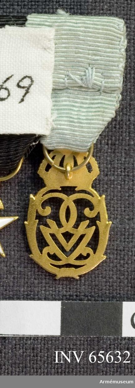 Grupp M II. Jubileumsminnestecken, krönt monogram i guld. Ljusblått medaljband.
