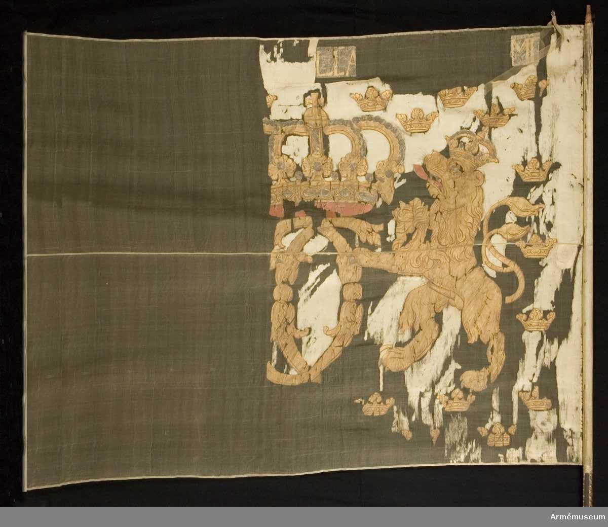 Duk: Tillverkad av vit taft. Duken fäst med guldband och förgyllda spikar.  Dekor:  Målat med guld lika på båda sidor: Karl XII:s namnchiffer, stort dubbelt C under sluten kunglig krona. Namnchiffret hålls av två krönta, dubbelsvansade lejon.  Stång av mörkbrun furu.