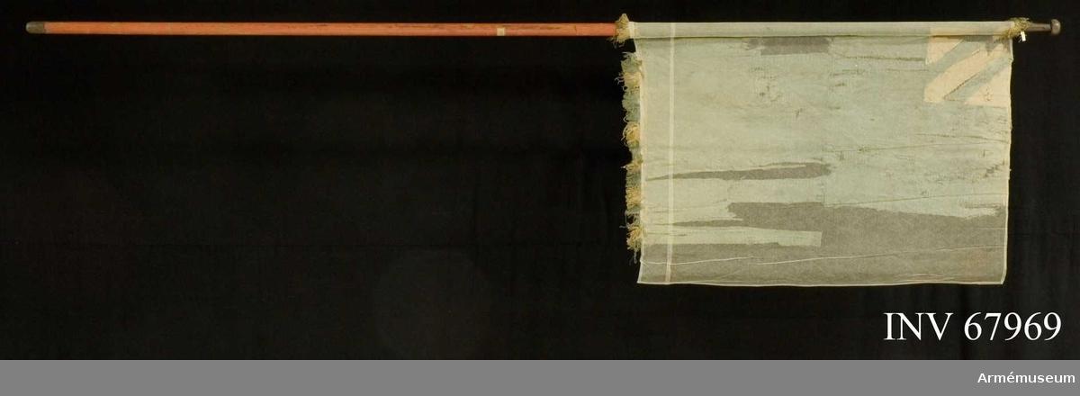 Duk: Tillverkad av blå och vit sidendamast.  Dekor: Damastmönster. I övre inre hörnet med påsydda vita (gula, röda?) fält, även dessa av sidendamast.  Frans: Rester av blå och vit ensidig frans, nedtill på fanduken.  Stången rödmålad. Holk men ej spets. Liten doppsko i metall.