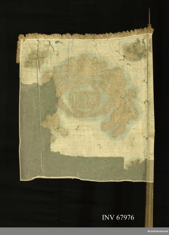 Duk: Enkel, tillverkad av linnelärft, ursprungligen blå (?). Duken fäst vid stången med en rad tennlikor.  Dekor: Målad (någorlunda läsbart endast på dukens utsida), två upprättstående lejon hållande Karl XII:s av öppen krona krönta spegel monogram, allt (guld) gult med mörkare brun kontur; endast det inre lejonet helt, de undre hörnkronorna borta.   Frans: Grov, enkel, av vitt (urspr.blått?) linne.   Stång av furu, kanellerad, blågråmålad; spets och holk av järn, holk med förlängda skenor nerpå stången och lansettformad spets.