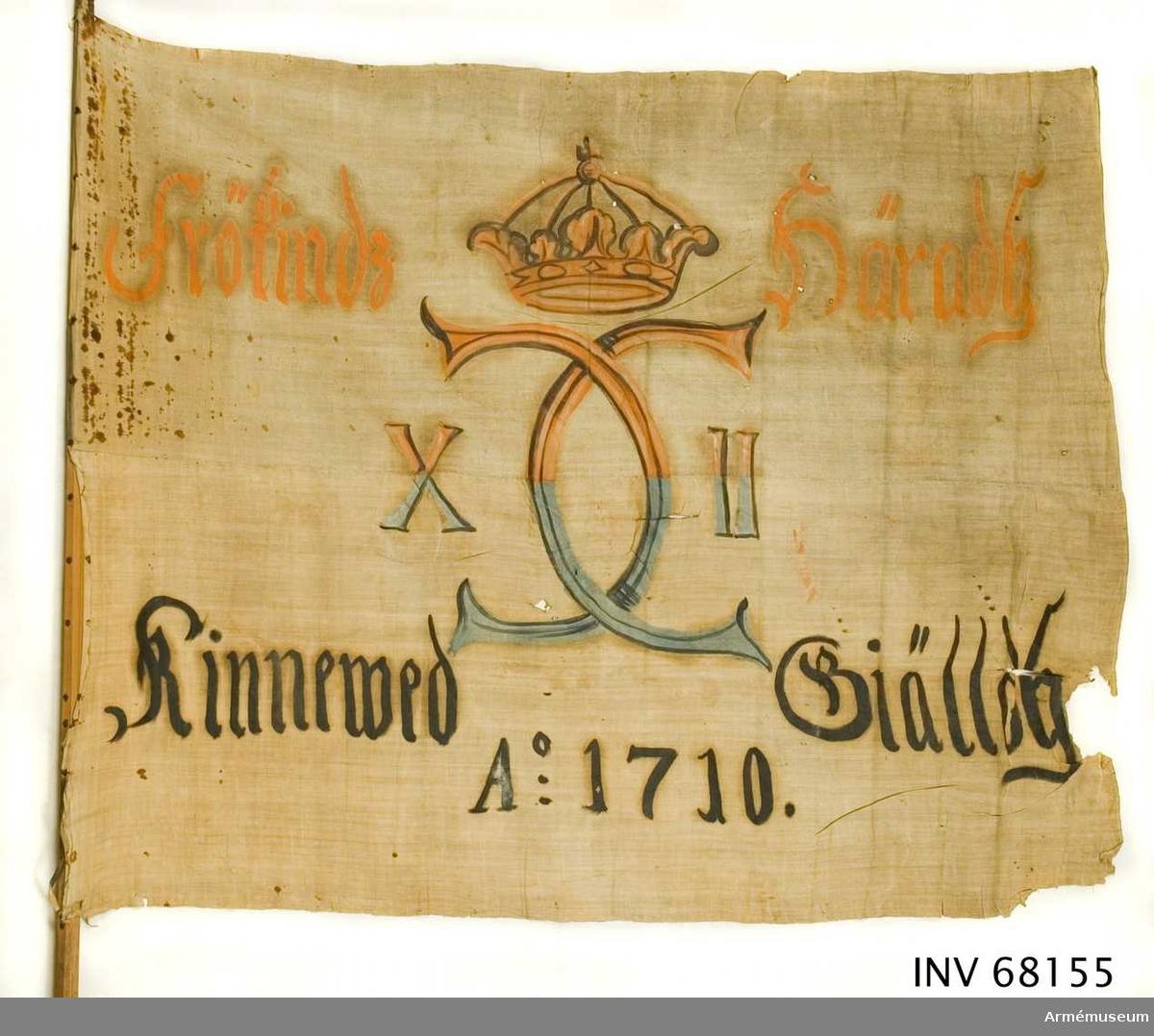 Duk: Tillverkad av enkel vit linnelärft, sydd av två horisontella våder. Fäst vid stången med en rad järnnagel på ett litet band av skinn.  Dekor: Målad i mitten, endast på dukens insida, Karl XII:s namnchiffer, dubbelt C, på ömse sidor om dessa X - II, krönt med sluten krona, i gult och brunt på den övre våden och på den nedre i blått och svart. Text på ömse sidor om chiffret, upptill i gult och nedtill i svart. Under chiffret text i svart.  Stång: Åttkantig stång av furu. Holk och spets i ett av järn. Två stycken stjärnbeslag.