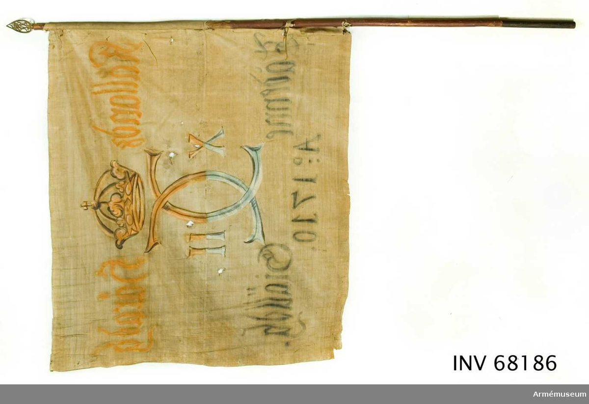 Duk: Tillverkad av enkel vit linnelärft, sammankastad med kastfållen åt insidan. Vertikala ytterkantsfållen åt utsidan. Har varit fastsydd runt stången.  Dekor: Målad endast på dukens insida, dock namnchiffret och kronan ifyllt på utsidan, Karl XII:s namnchiffer, dubbelt C, krönt med sluten krona. På ömse sidor om chiffret X-II. Övre våden i gult och brunt, nedre i blått och svart, mycket blekt nästan vitt. Text på ömse sidor om chiffret, upptill i gult och nedtill i svart. Under chiffret text i svart.  Stång: Tillverkad av trä och rödmålad.