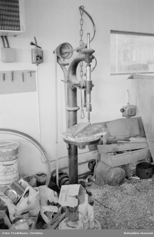 """Motivbeskrivning: """"Båtbyggare Henry Josefsson, Klöverön, Marstrand. Interiör från båtbyggarverkstaden F.d ladugård). Pelarborrmaskin."""" Datum: 19800919"""