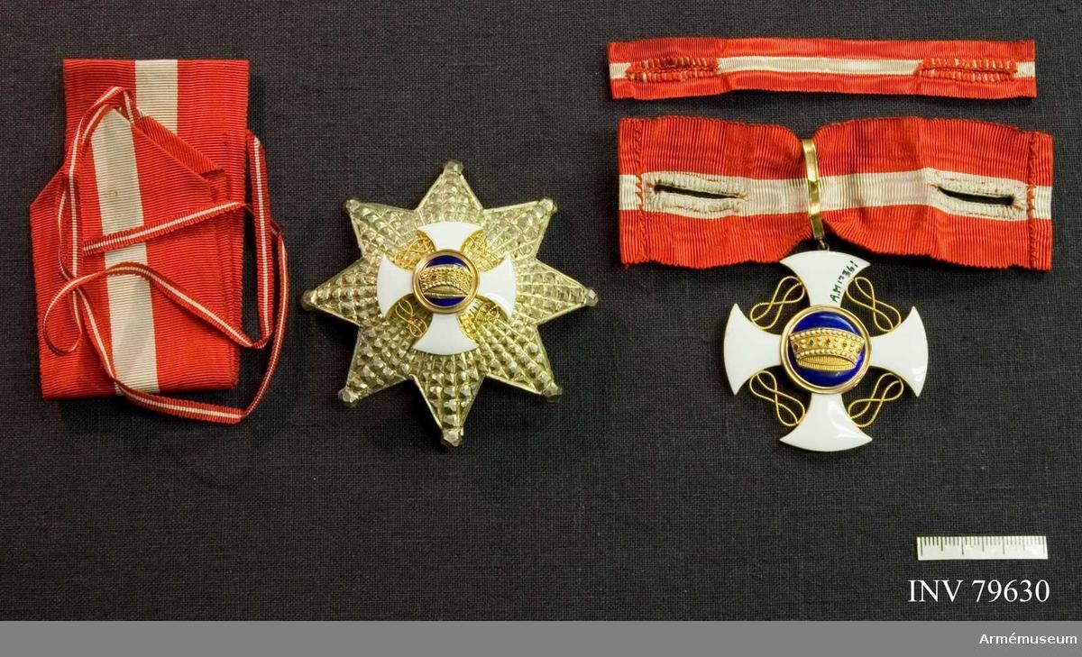 """Grupp M.   1) Ordenstecknet utgöres av ett guldinfattat, vitemaljerat kors, vars armar äro något kupiga, på yttersidan rundade och mot mitten likaledes rundat avsmalnande. Mellan armarna slingrar sig ett guldsnöre i s.k. kärleksknutar. Åtsidan: Den guldkantade mittskölden av blå emalj visar den italienska """"järn""""-kronan. Frånsidan: Mittskölden, likaledes guldkantad, gul, hamrad, uppbär en krönt svart örn med utspärrade vingar; på bröstet Savoyens vapen, ett vitt kors i rött fält. 2) Kraschanen är 8-uddig, facetterad, av silver med kulor i spetsarna; i mitten är lagd en i mindre format framställd ordensstjärna, sedd från åtsidan.  Literatur: Beskrivning över ordnar. A.M. bibliotek Litt XII. B. n:r 44."""