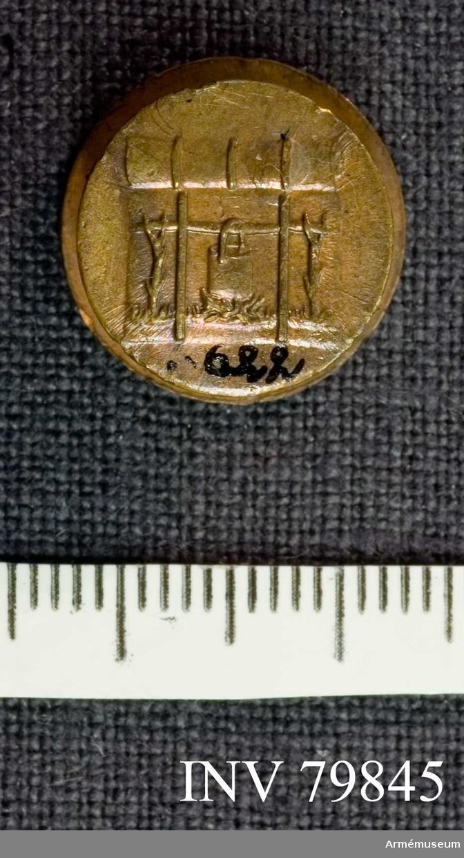 Grupp M. Minnestecknet består av en liten rund dubbelknapp. Åtsidan lika med den del av n:o 6621, som utgöres av den runda medaljens åtsida. Denna lilla ensidiga medalj är med en stolpe förenad med en något mindre dylik. På frånsidan av den senare synes tydligare än på n:o 6621 en där beskriven kokinrättning. Därovanför något som liknar ett hoprullat större tygstycke. /Beskrivning av Prn.