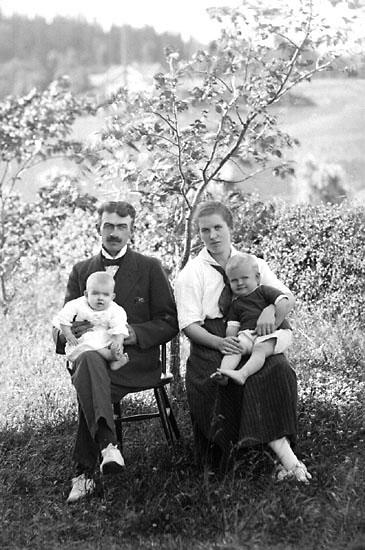 """Enligt senare noteringar: """"Familj sittande på pinnstolar i trädgård. Rudolf i Närestad.  Kortet taget den 10 augusti 1920."""" (BJ)"""
