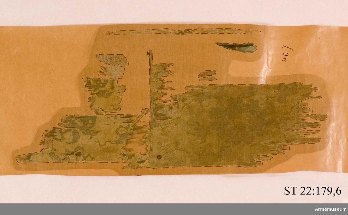 Duk av grön kinesisk sidendamast. Ur ett moln en hand hållandes ett nedåtgående svärd. Runtom den ryska St Andreas orden i målad guldkedja. Allt inramas av palmblad i vit sidenbaiberek. Stången grönmålad ovan greppet och röd nedom. Spetsen saknas.